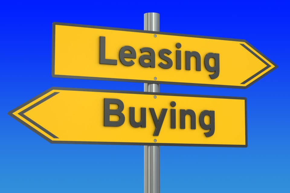 Road sign arrows pointing toward buying and leasing