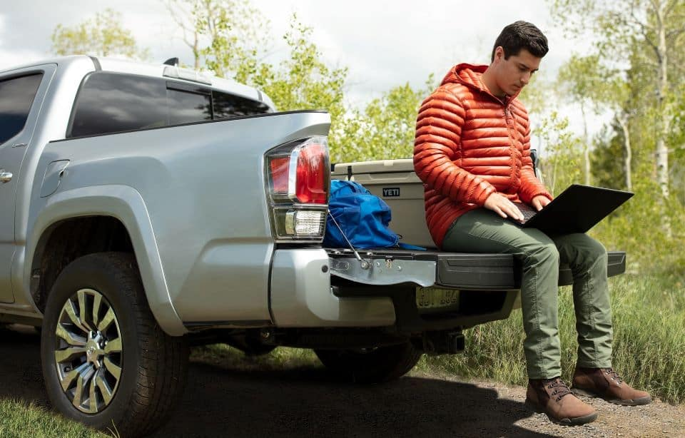 a 2020 Toyota Tacoma parked outdoors with a man sitting on the tailgate using a laptop.