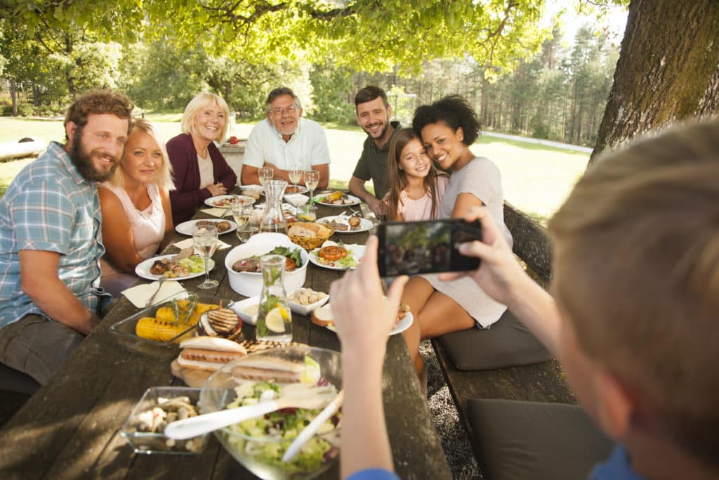 child taking photo of family at outdoor dinner table