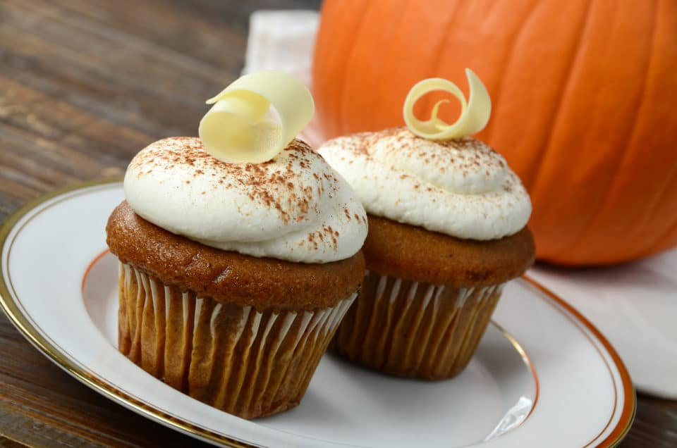Two pumpkin cupcakes on a plate next to a pumpkin in the background