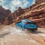 A blue 2020 Toyota Prius driving through a canyon.