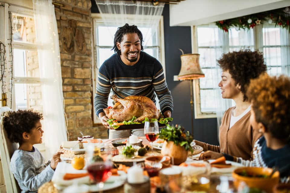 Happy black father bringing Thanksgiving turkey to the table.