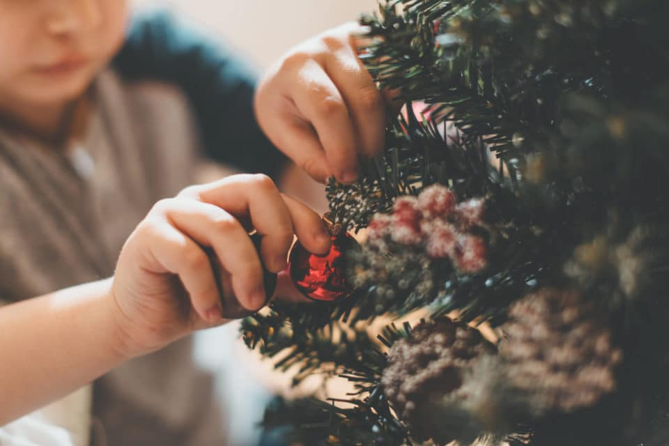 A boy hanging ornaments on a Christmas tree