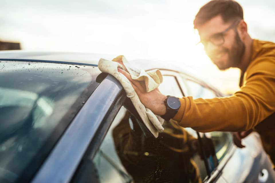 Man cleaning exterior of car