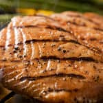 Close up of a grilled salmon filet on charcoal grill with asparagus