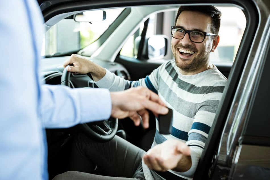 Happy man receiving keys to test drive a vehicle