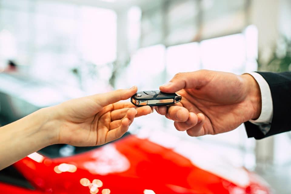 Handing of car keys. The car seller passes the keys to the dealership.