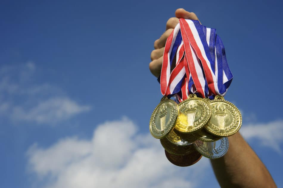 Hand holds up a bunch of gold, silver, and bronze medals