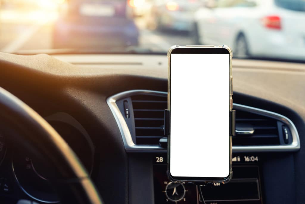 white screen of smartphone mounted on car's dashboard