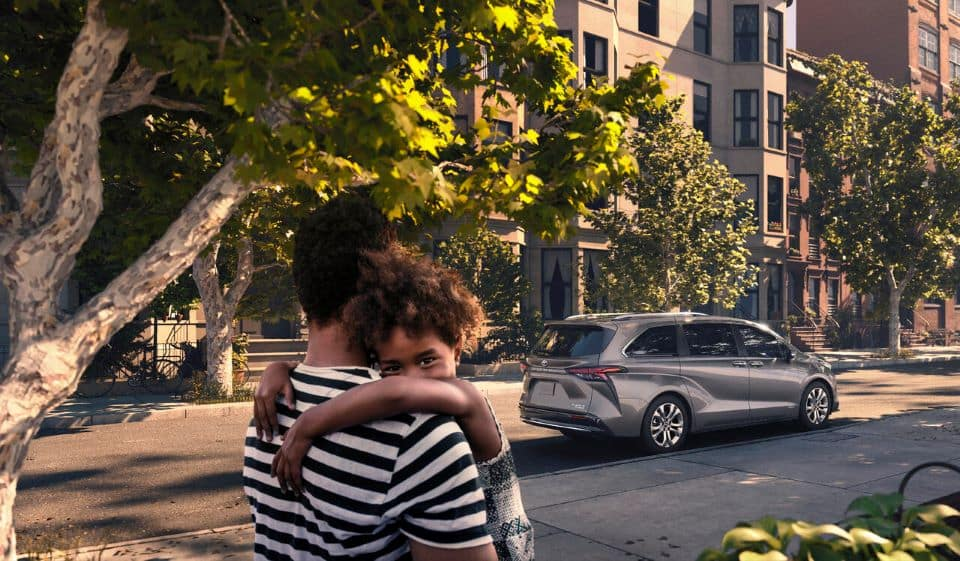 A father and daughter standing on the sidewalk under a tree, their 2021 Toyota Sienna minivan is in the background