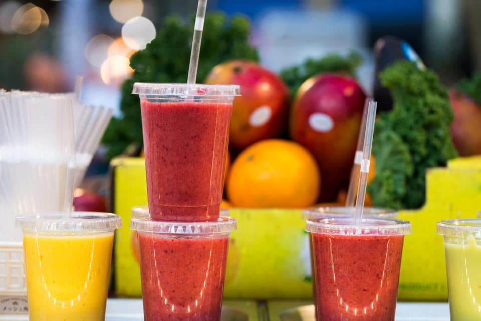 Close up color image depicting freshly made fruit juices and smoothies on display in a row