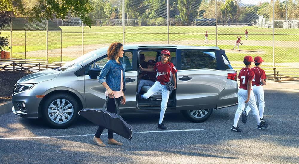 2018 Honda Odyssey parked outside a baseball field with kids getting out