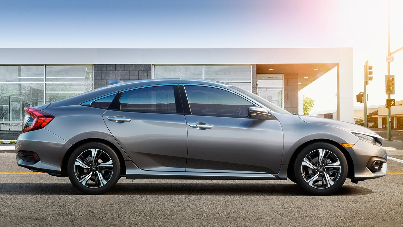 Side View of the 2017 Honda Civic in Front of a Modern Building with a Solar Glare in the Top Right Corner