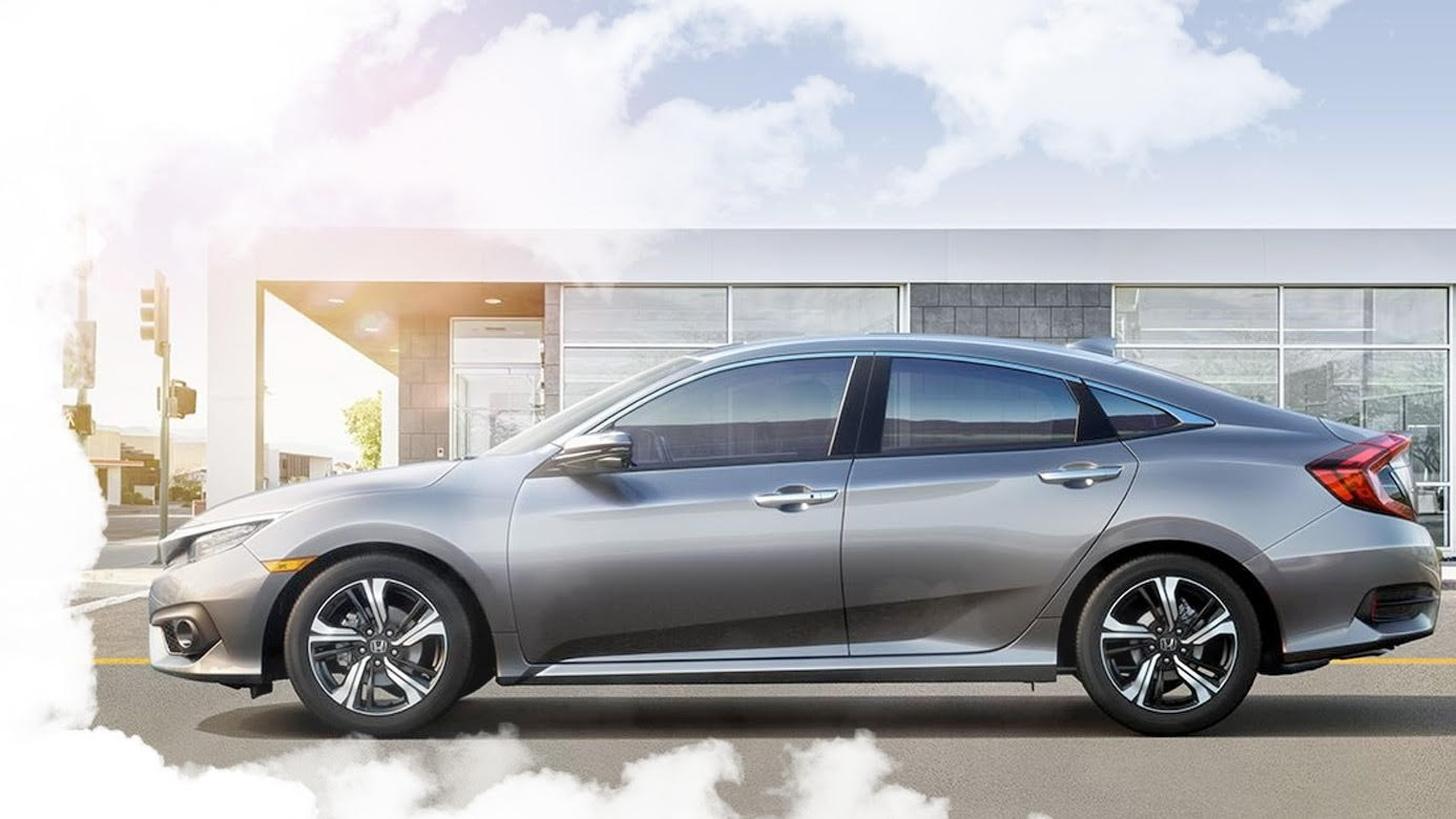 Side View of the 2017 Honda Civic Surrounded by Clouds in Front of a Modern Building