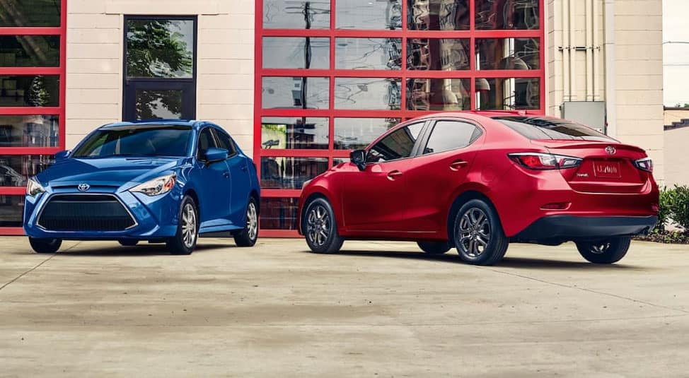 A blue 2019 Toyota Yaris is parked next to a red one outside of a building with red garage