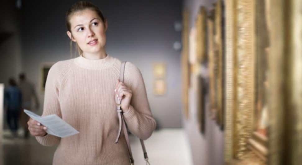 A young woman is holding a brochure at an art museum.
