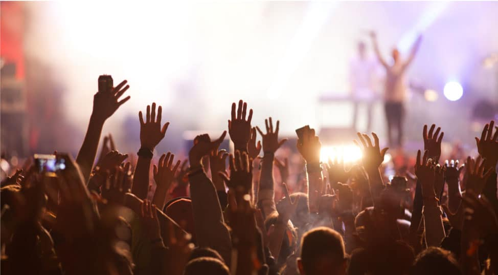A crowd has their hands up at a concert