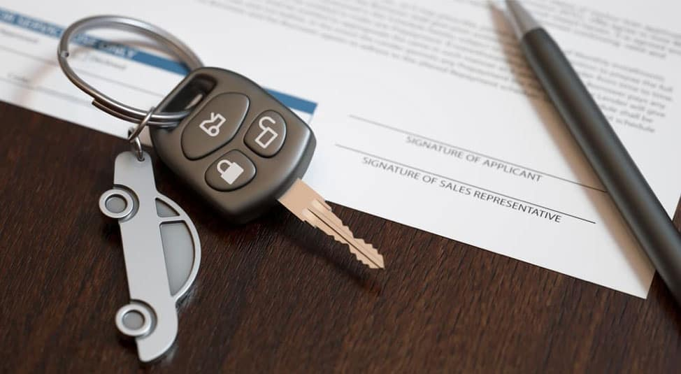 A car key is on top of a car loan agreement with a pen.