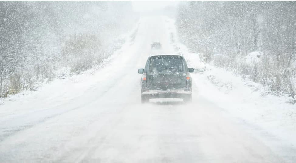 An SUV is driving on a highway in Milwaukee, WI, during a snow storm.