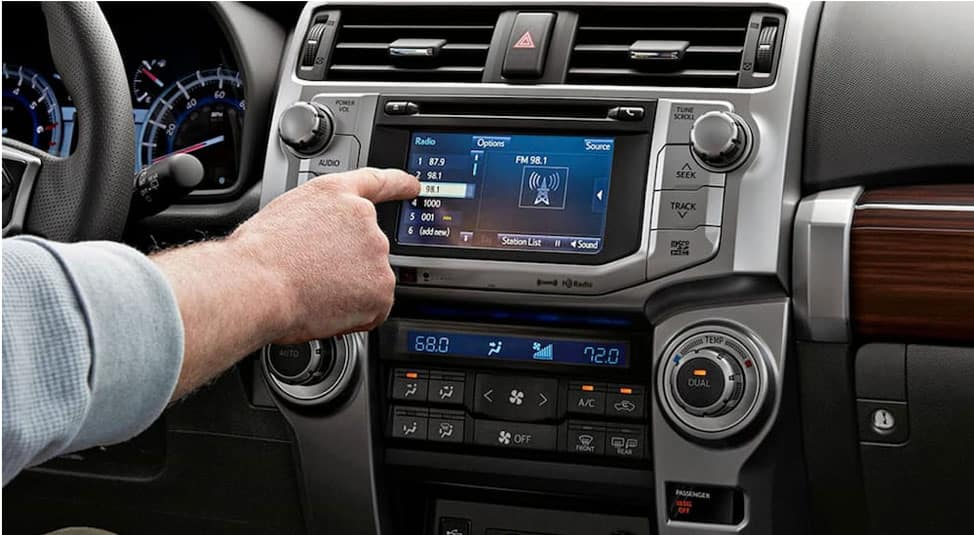 A man is changing the radio station on his 2019 Toyota 4Runner, popular among used cars in Milwaukee, WI, using the Entune infotainment system.
