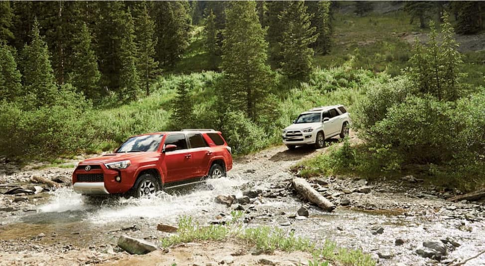A white 2019 4Runner is following a red one through a stream while on a trail