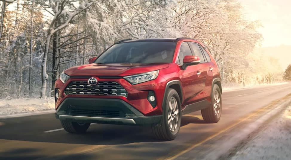 A red 2019 Toyota RAV4, popular among used SUVs in Milwaukee, is driving on a snowy road.