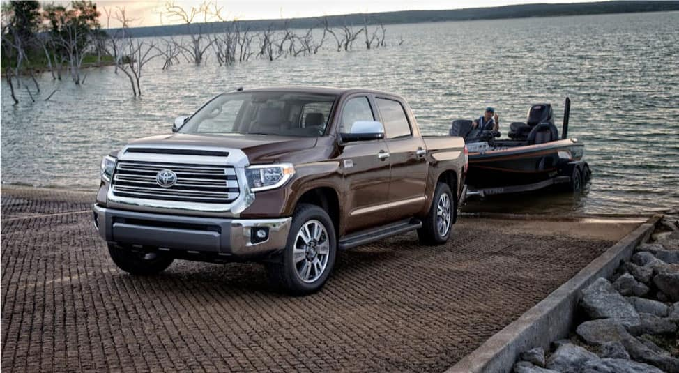A brown 2019 Toyota Tundra is pulling a small boat out of the water.