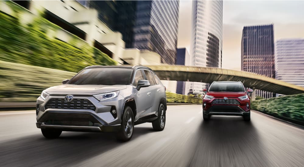 A silver 2019 RAV4 is driving in front of a red 2019 RAV4 on a city highway.